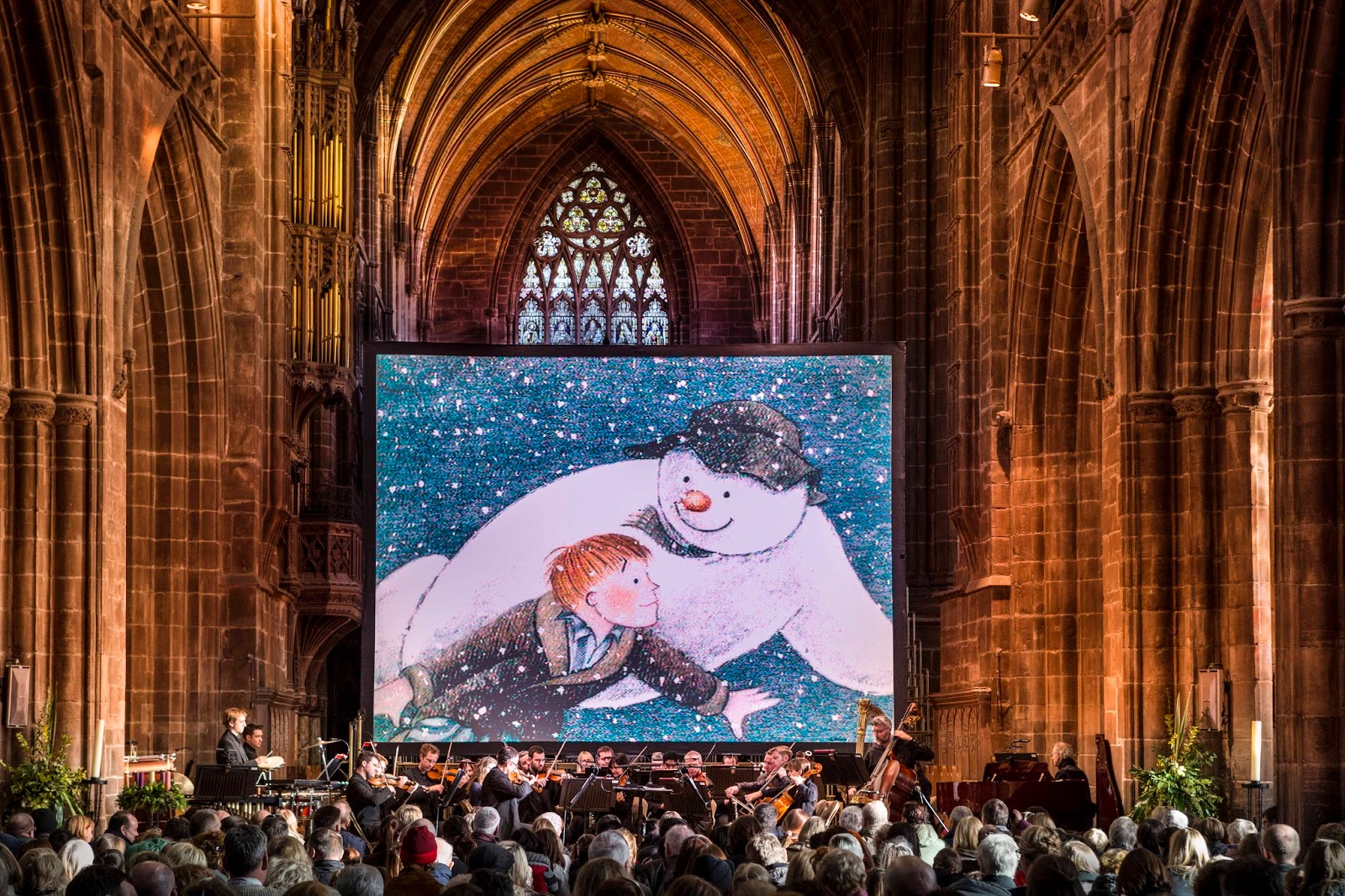 audience watching the snowman film on a large screen in the cathedral with a large orchestra playing in front of the screen