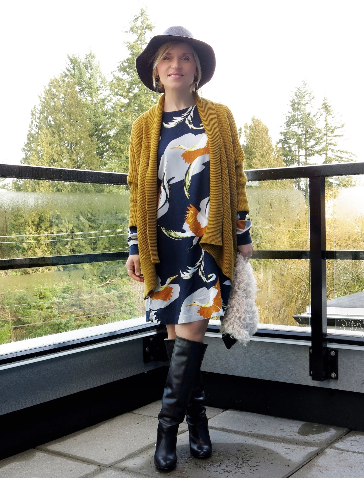 styling a printed shift-dress with a drapey cardigan, knee boots, and a floppy hat