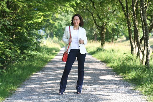 Женщина за 50 в белом жакете, джинсах с красной сумкой