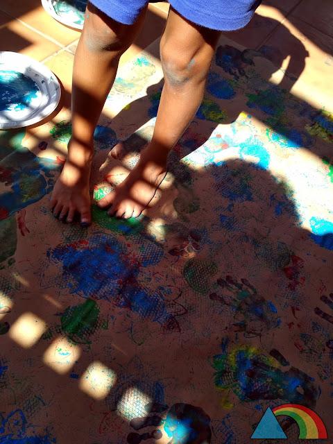 Pintando con los pies sobre un papel extendido en el suelo, con pintura de dedos