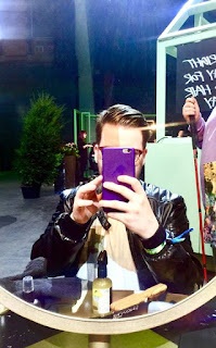A selfie of me including slicked back quiffed brown hair, a black leather jacket, a grey oversized flannel shirt and a purple cased phone in a circular mirror on a bright background