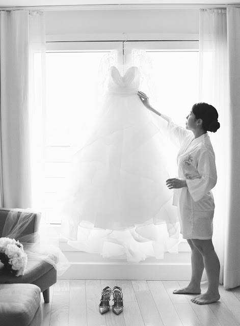 Jin adjusts her wedding dress hanging in the window on the morning of her Bridgeview Yacht Club wedding