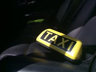 Taxidachzeichen liegt auf der Rückbank im Taxi