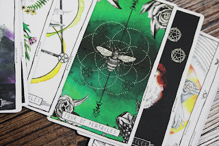 A photo of tarot cards spread out across a wooden surface, with the four of pentacles on top - a dark green card, with a wasp in the center, surrounded by interlinking circles made from white polka dots, and four black pentacles