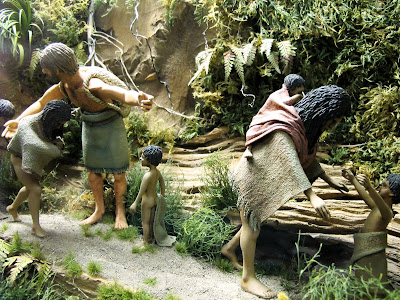 Diorama of a 19th-century Maori family being guided along a track in the bush by a pakeha man.