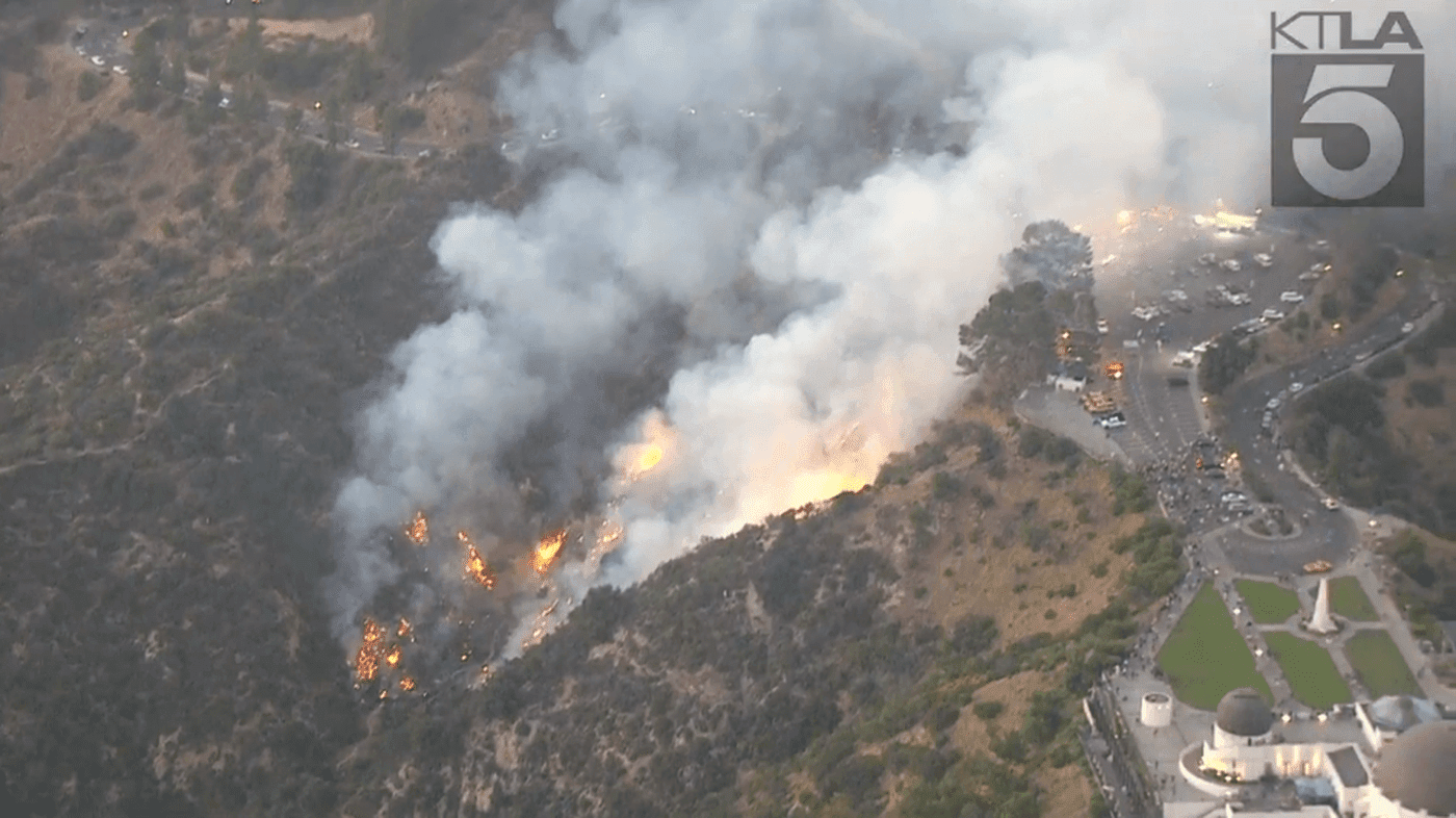 Brush fire burns up the hillside below Griffith Observatory