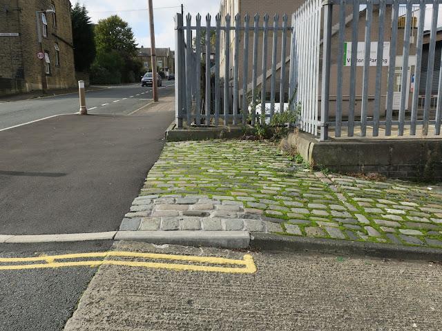 Moss between cobbles, yellow lines, railings, car