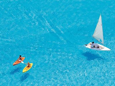 Pessoas remando de caiaque e navegando em barco a vela