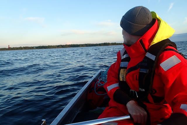 Ihminen soutuveneessä, Ulkokrunnin pooki taustalla kaukana.