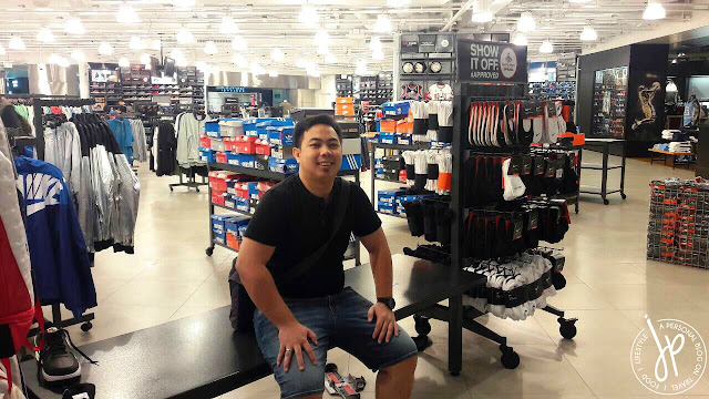 man sitting on bench at athletic shoe store