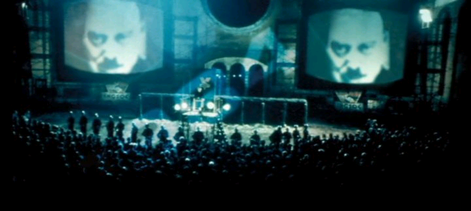 Big Brother's face looms on giant telescreens in Victory Square in one of several scenes of Michael Radford's 1984 film adaptation of George Orwell's Nineteen Eighty-Four.