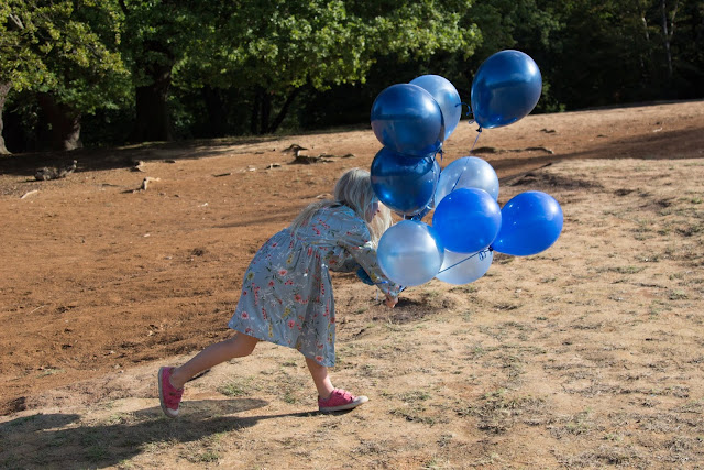 A girl wrestling with a bunch of balloons