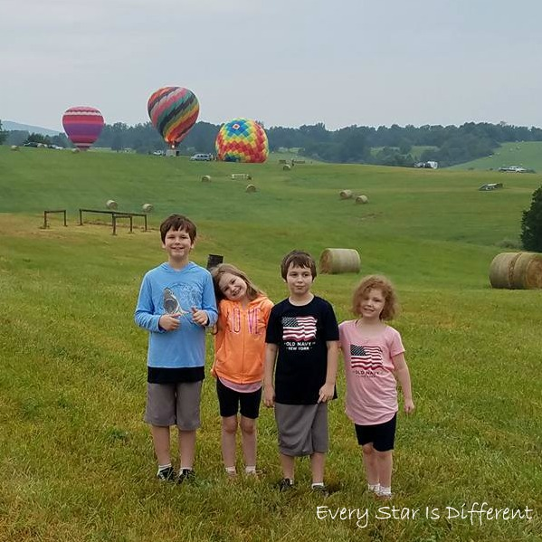 Four kiddos watching the hot air balloon festival.