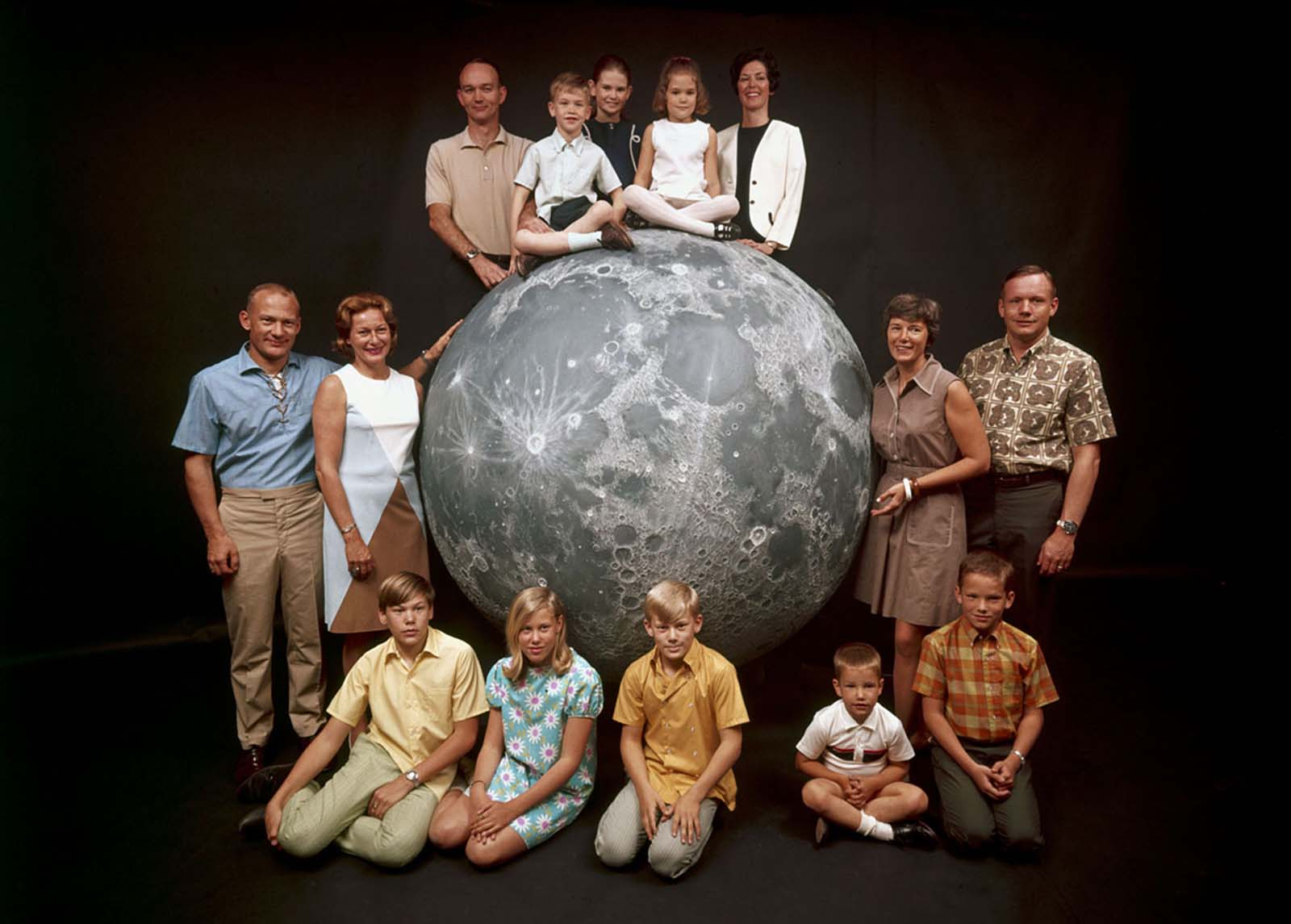A group portrait of NASA's Apollo 11 astronauts posing with their families around a model of the moon in March 1969. Pictured are: (at top, from left) the astronaut Michael Collins; his children, Mike, Kate, and Ann; and his wife, Pat; (at left) the astronaut Buzz Aldrin; his wife, Joan; and his children, Mike, Jan, and Andy; and (at right) the astronaut Neil Armstrong; his wife, Jan; and his sons, Ricky and Mark.