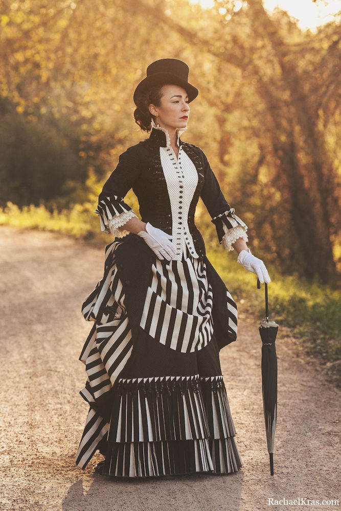 Woman in black and white striped victorian bustle dress with umbrella/parasol, gloves, and top hat