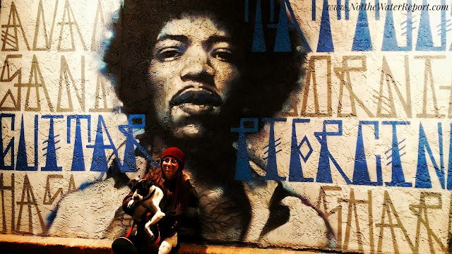 Street art mural of Jimi Hendrix. Woman holding dog in front.