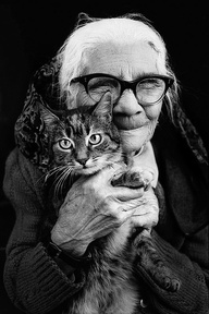 Beautiful black and white photo of an old lady with big glasses holding a kitten