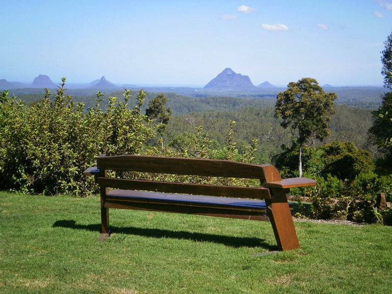 View of Glass House Mountains with bench seat in foreground