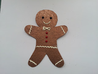 Gingerbread man shape embossed in copper and decorated with white paste and gems