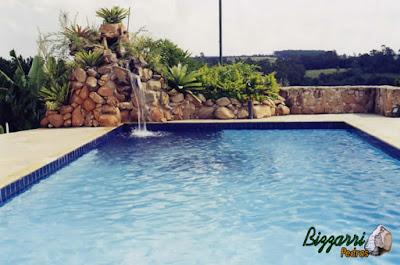 Construção da piscina em alvenaria com o revestimento de azulejo com a cascata de pedra com pedras ornamentais com a execução do muro de pedra.
