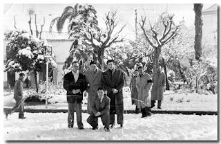 Nazarenos bien abrigados inmortalizan el momento sobre la nieve de Los Jardines. Tras ellos, a la derecha, se perfila la iglesia.