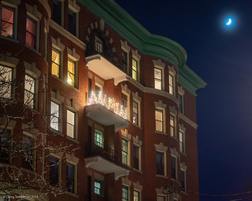 Portland, Maine USA December 2018 photo by Corey Templeton. A festive balcony, and a sliver of the moon in the distance, above Danforth Street.