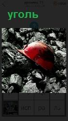 лежит уголь и каска красного цвета на верху