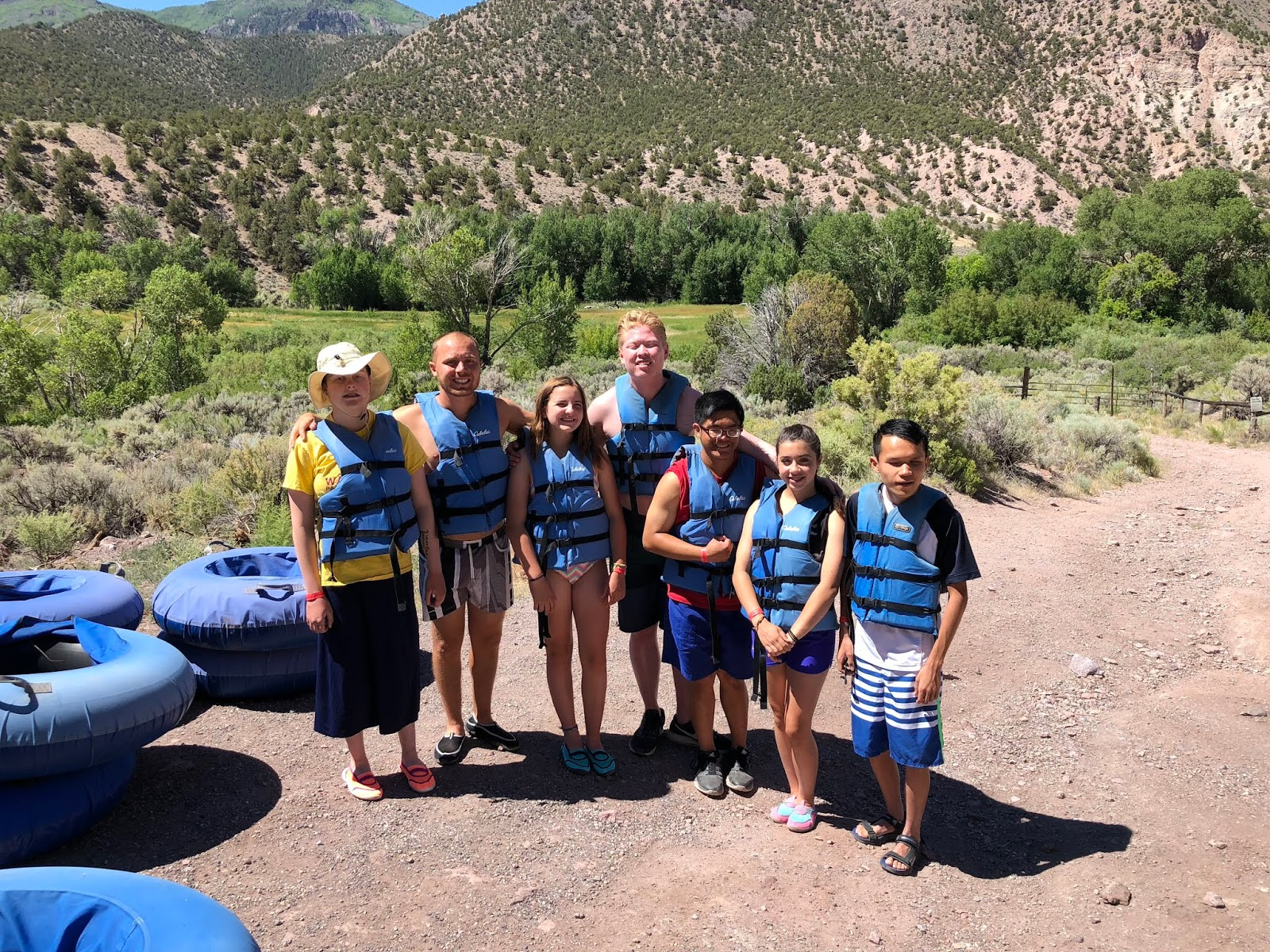 A group of female and male teenagers stand together with their life jackets on before going tubing in the river.