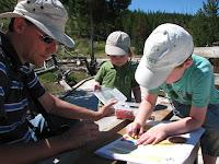 Papa en broer samen met Casper aan het werk in het Junior Ranger Activity paper voor de leeftijd van 5-7 jaar - Yellowstone National Park
