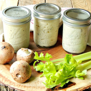 Cream soups in 1/2 pint jars on a round wooden platter with fresh mushrooms and celery.