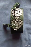 LoveLea's dark green leather bracelet with metal medallions&tassels, close up.