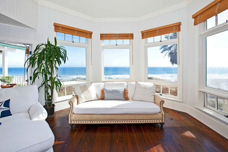 Coastal bedroom with raffia sofa and ocean view