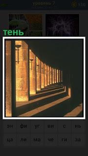 рядами стоят колонны и от них падает тень в солнечный день
