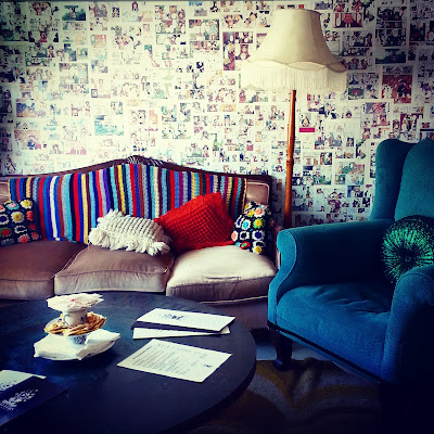 Retro living room with vintage sofa draped with a crocheted rug, and green wing chair with floor lamp behind it.