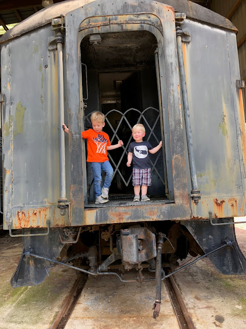 Two kids standing on the backside of an old train