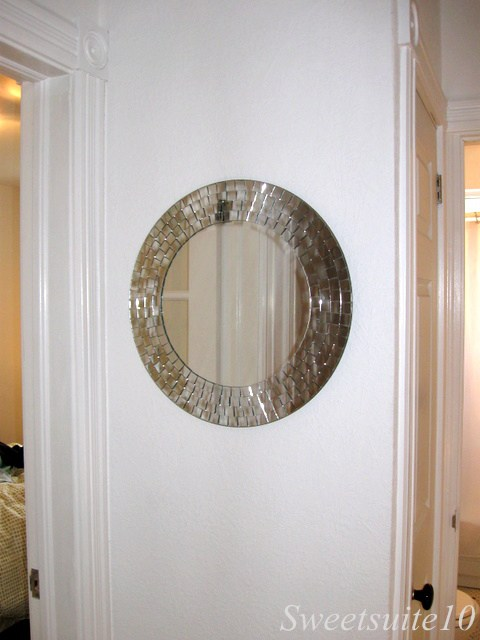 Round mirror hung on a white wall