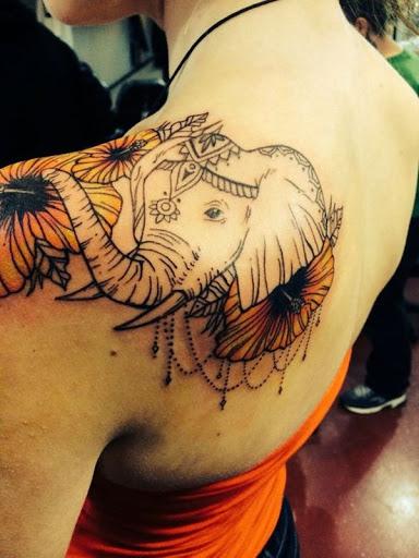 Um elefante com um cocar é adornado com um cocar, miçangas e flores.