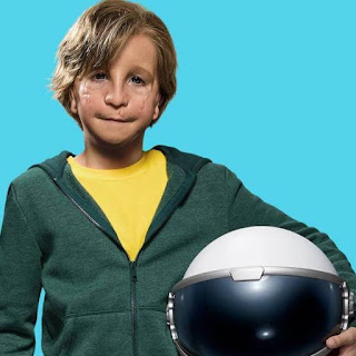 A boy holding a helmet while smiling