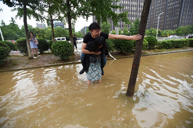 Woman Carries Her Boyfriend During Flood To Save His Leather Shoes From Soaking