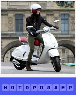 на улице девушка сидит на мотороллере в шлеме, готова ехать