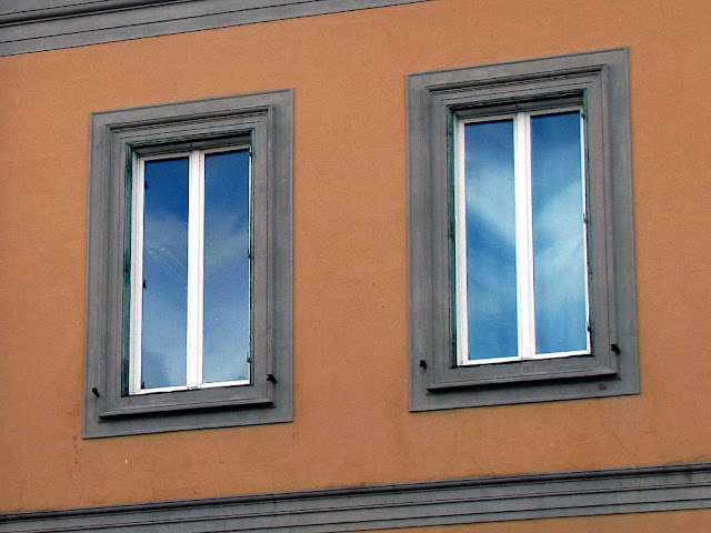 clouded sky reflected in two windows in Via Goldoni, Livorno