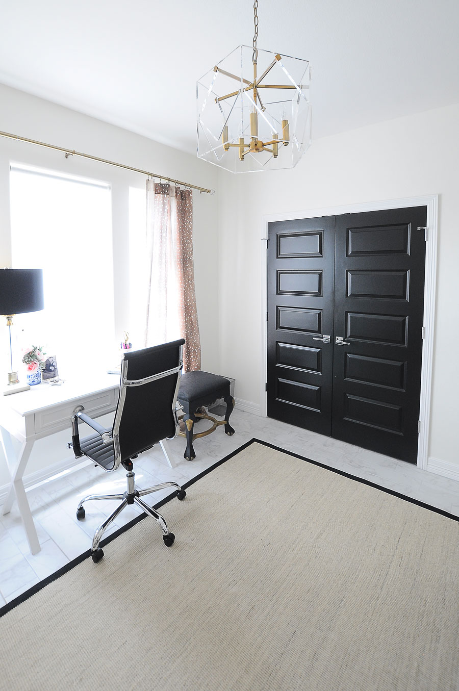 Black closet doors in a bright white and gold home office space.