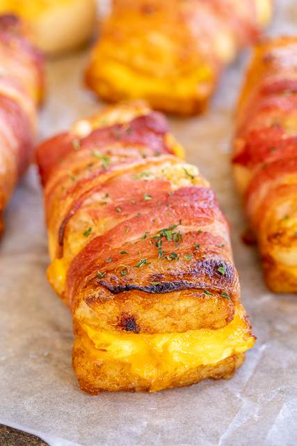 Bacon Wrapped Egg & Cheese Hash Browns - seriously DELICIOUS!!! Frozen hash brown patties stuffed with scrambled eggs and cheddar cheese and wrapped in bacon. Best breakfast EVER!!! Can make as many as you need at a time. Can assemble ahead of time and refrigerate or freeze for later. #breakfast #brunch #hashbrowns #bacon #baconeggcheese #freezermeal