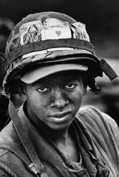 Young black soldier with playing cards strapped to his helmet. Vietnam War. Impossible Wars. marchmatron.com