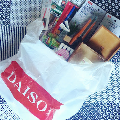 Plastic Daiso bag filled with purchases, on a black and white Japanese-print bedspread.