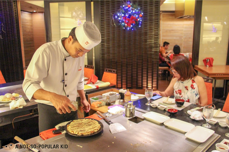 Chef completing the okonomiyaki dish in Kimpura Restaurant