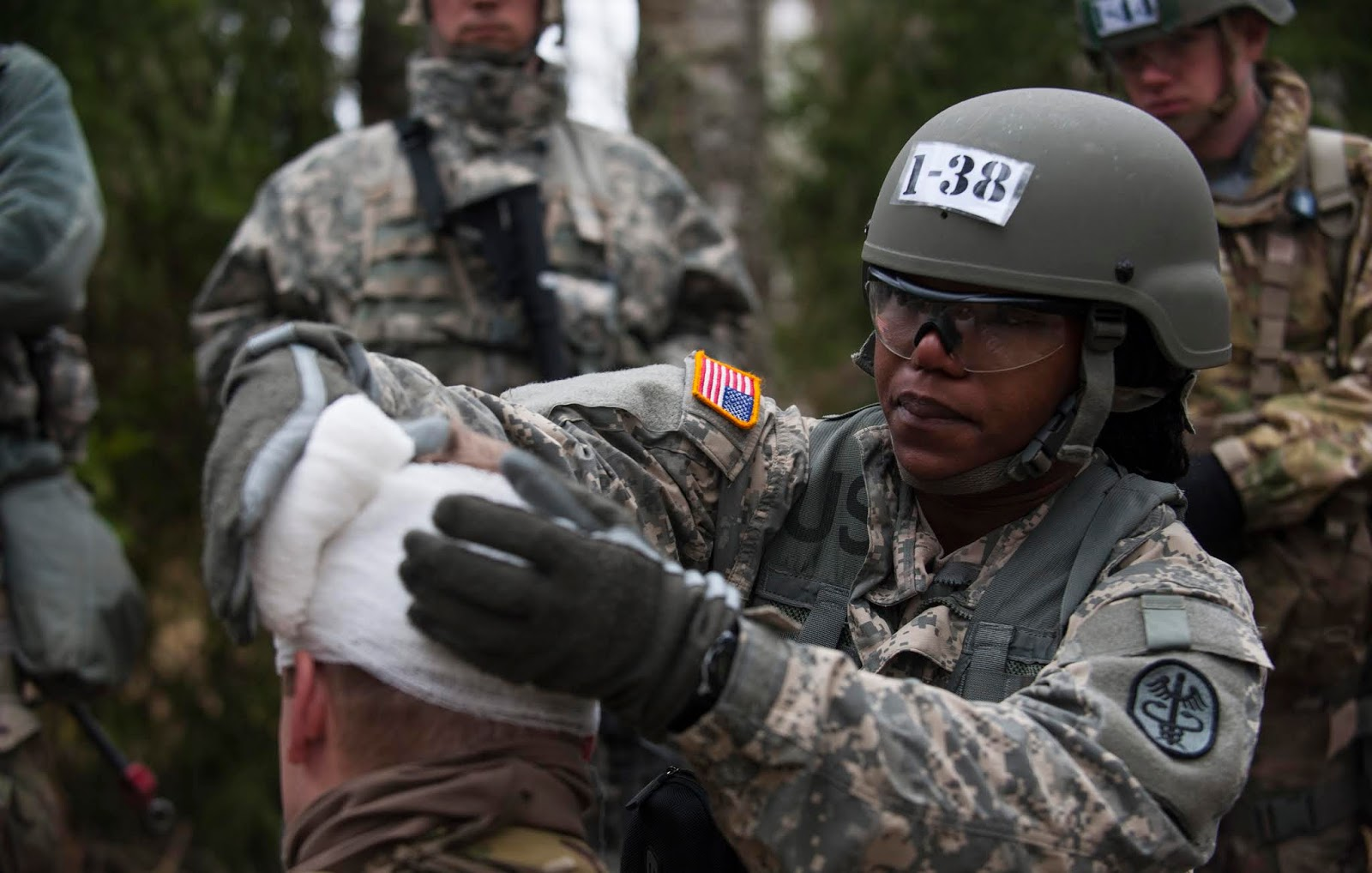 woman soldier bandaging a man's head