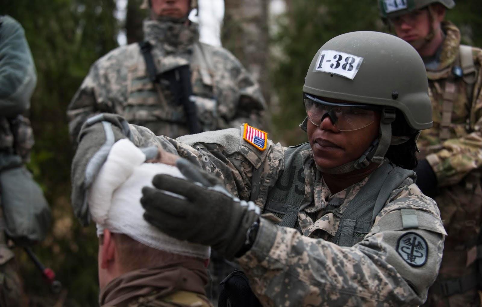 woman soldier bandaging a man's head