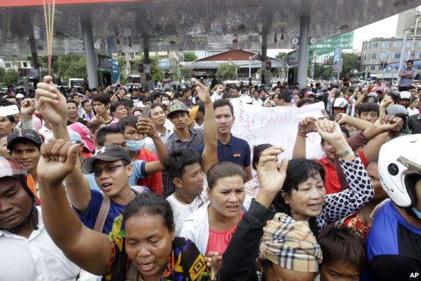 Cambodians shout slogans outside a shopping mall where prominent political analyst Kem Ley was shot dead in Phnom Penh, Cambodia, July 10, 2016.