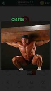 сильный мужчина держит над головой тяжелый груз